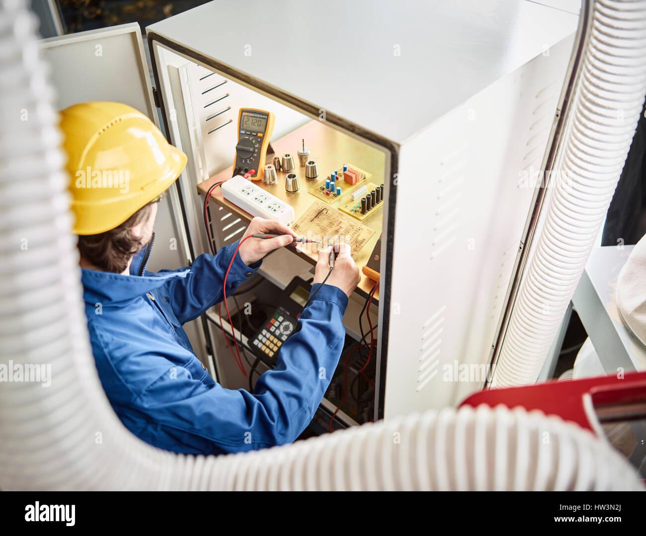 Ingenieur mit Helm während einer Reparatur und Fehlerbehebung der Steuerung einer CNC-Maschine, Österreich Stockbild