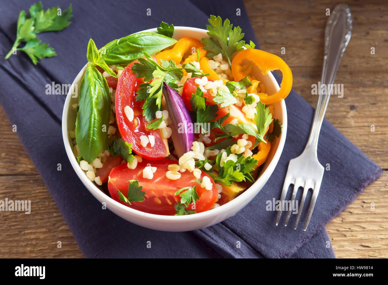 Frische Bio-Tomaten und Bulgur Couscoussalat Taboulé mit Gemüse und grünen - gesunde vegetarische Stockbild