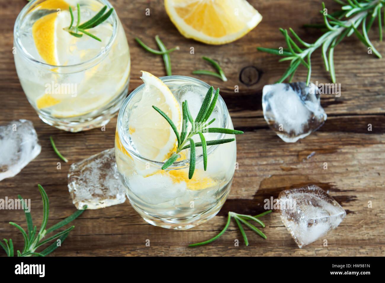 Alkoholische Getränke (Gin Tonic Cocktail) mit Zitrone, Rosmarin und Eis am rustikalen Holztisch, Textfreiraum Stockbild