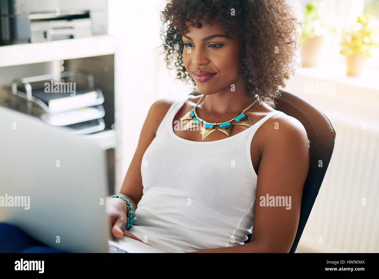 Junge hübsche Brünette auf kleine Unternehmen Computer arbeiten und lächelnd auf im Hintergrund unscharf. Stockbild