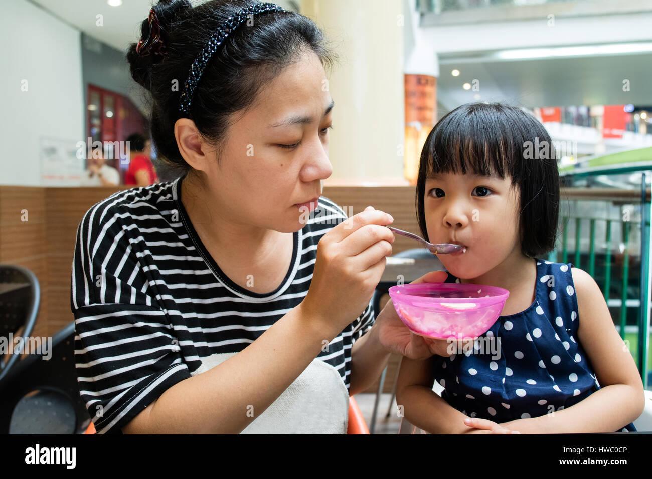 Asiatische Mutter füttert ihre Tochter im Café im freien Stockbild