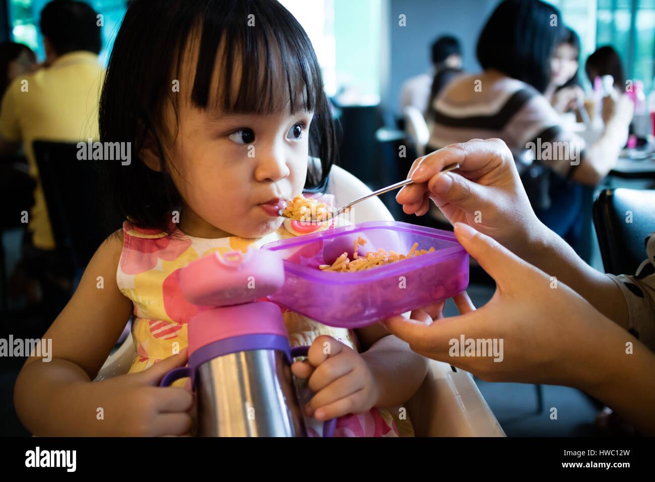 Asiatische Mutter füttert Kind Tochter Essen in einem Restaurant Stockbild