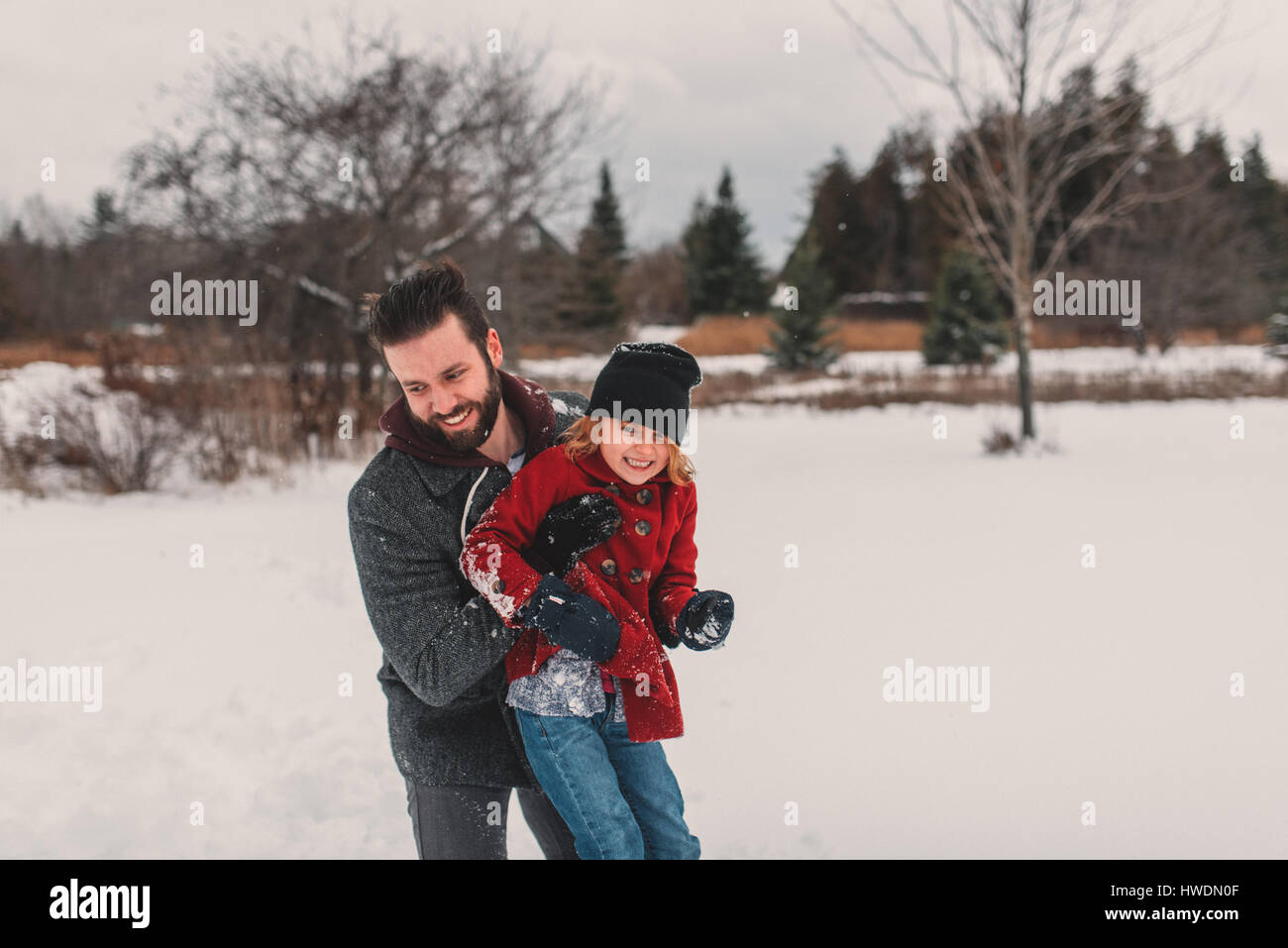 Vater und Tochter spielen im Schnee Stockbild