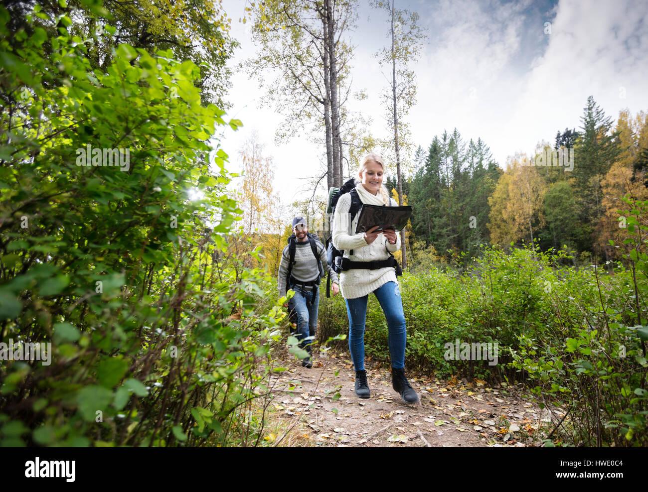Junge Frau mit Karte beim Wandern mit Freund Stockbild