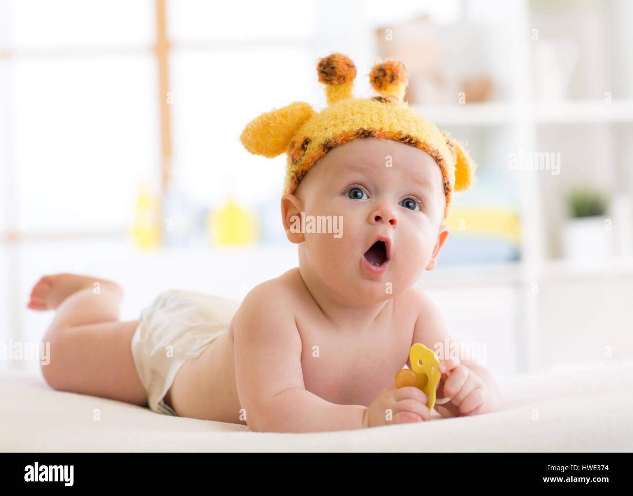 lustige baby junge giraffe hut liegen auf dem bauch im kindergarten kleines kind liegt im bett. Black Bedroom Furniture Sets. Home Design Ideas