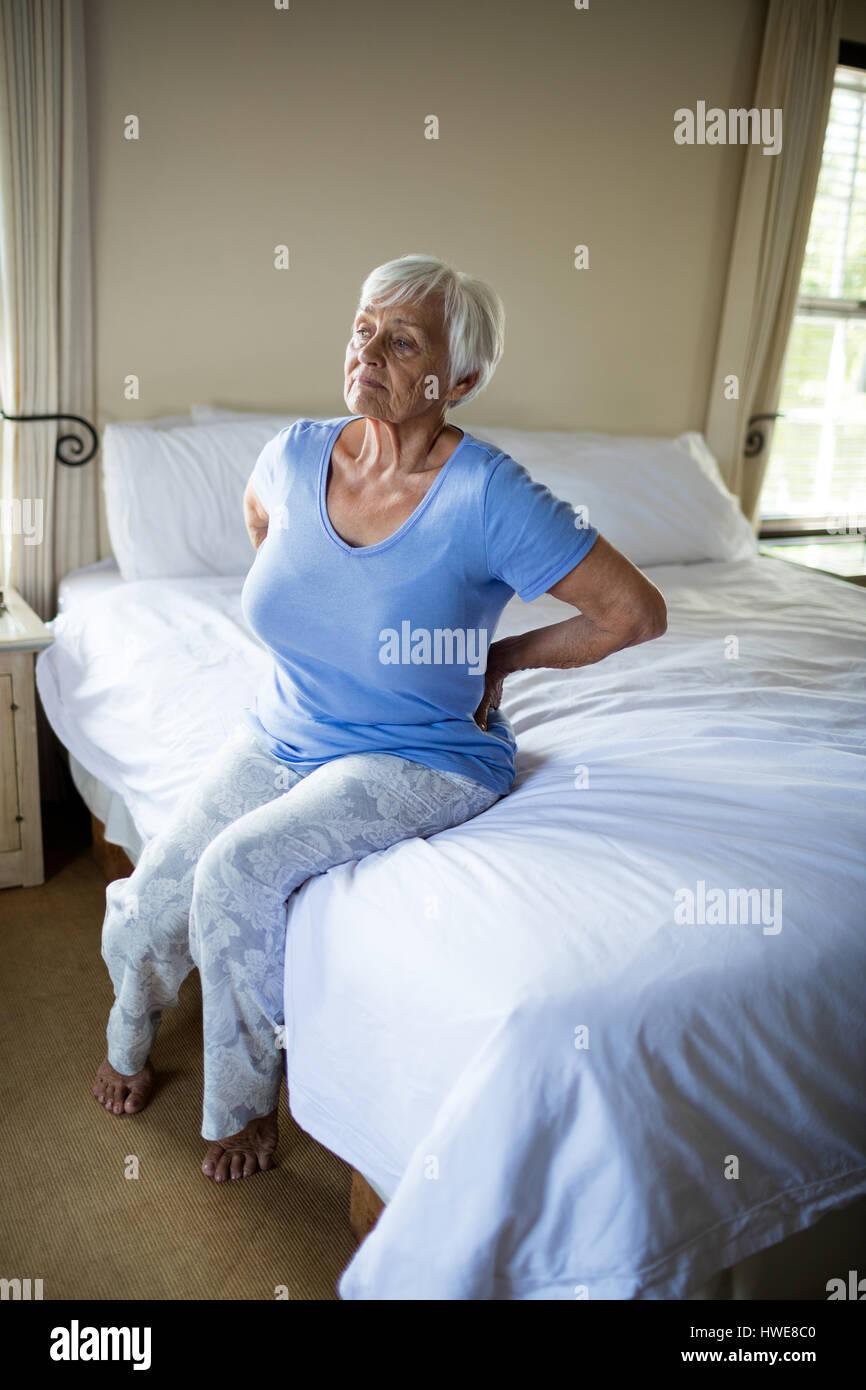 Ältere Frau, die leiden unter Rückenschmerzen im Schlafzimmer zu Hause Stockbild