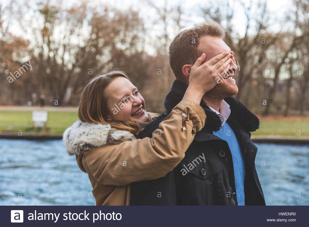 Junge Frau für Freundes Augen am Park am Flussufer Stockbild
