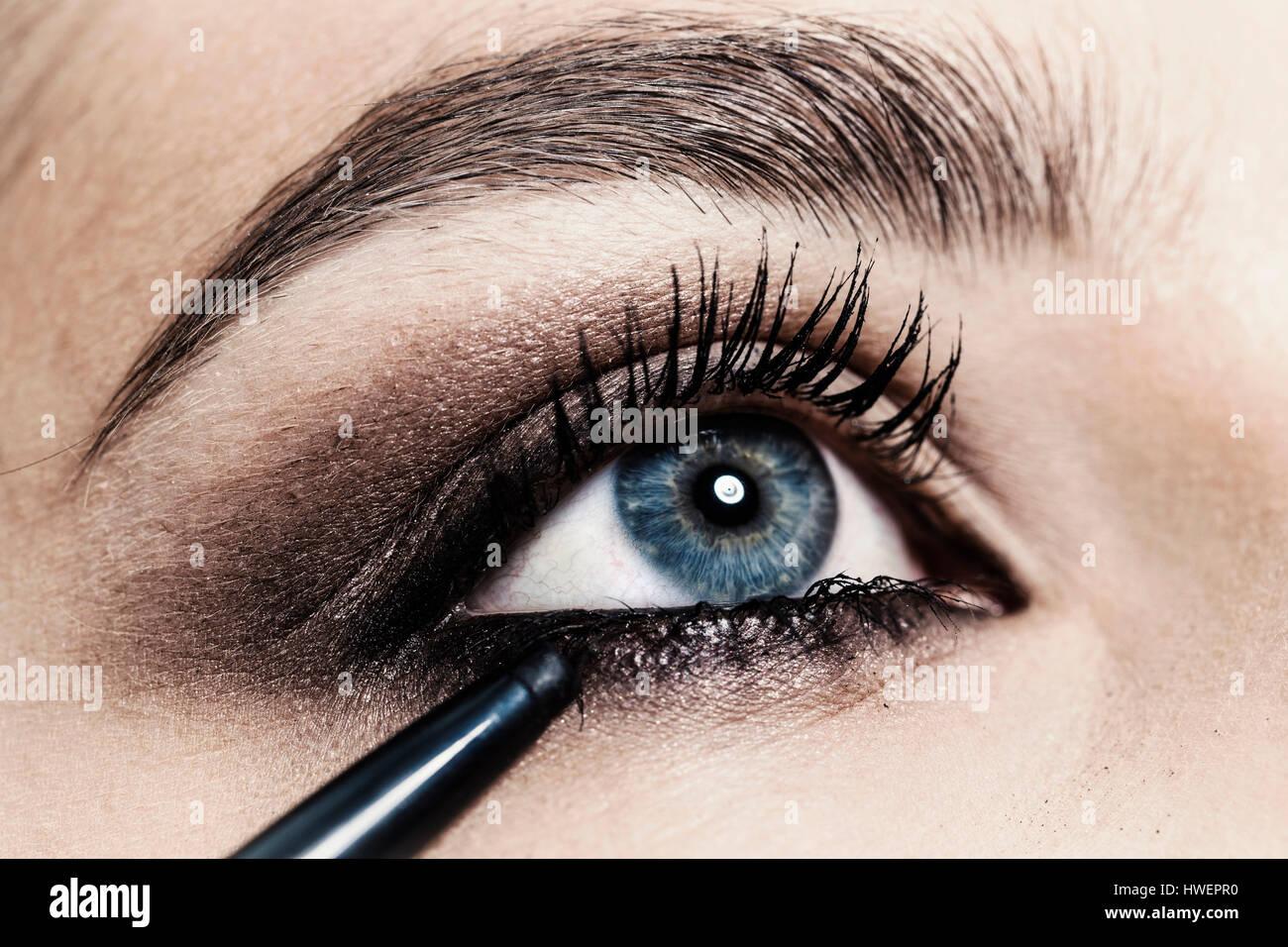 Nahaufnahme der Eyeliner auf junge Frau Auge angewendet wird Stockbild