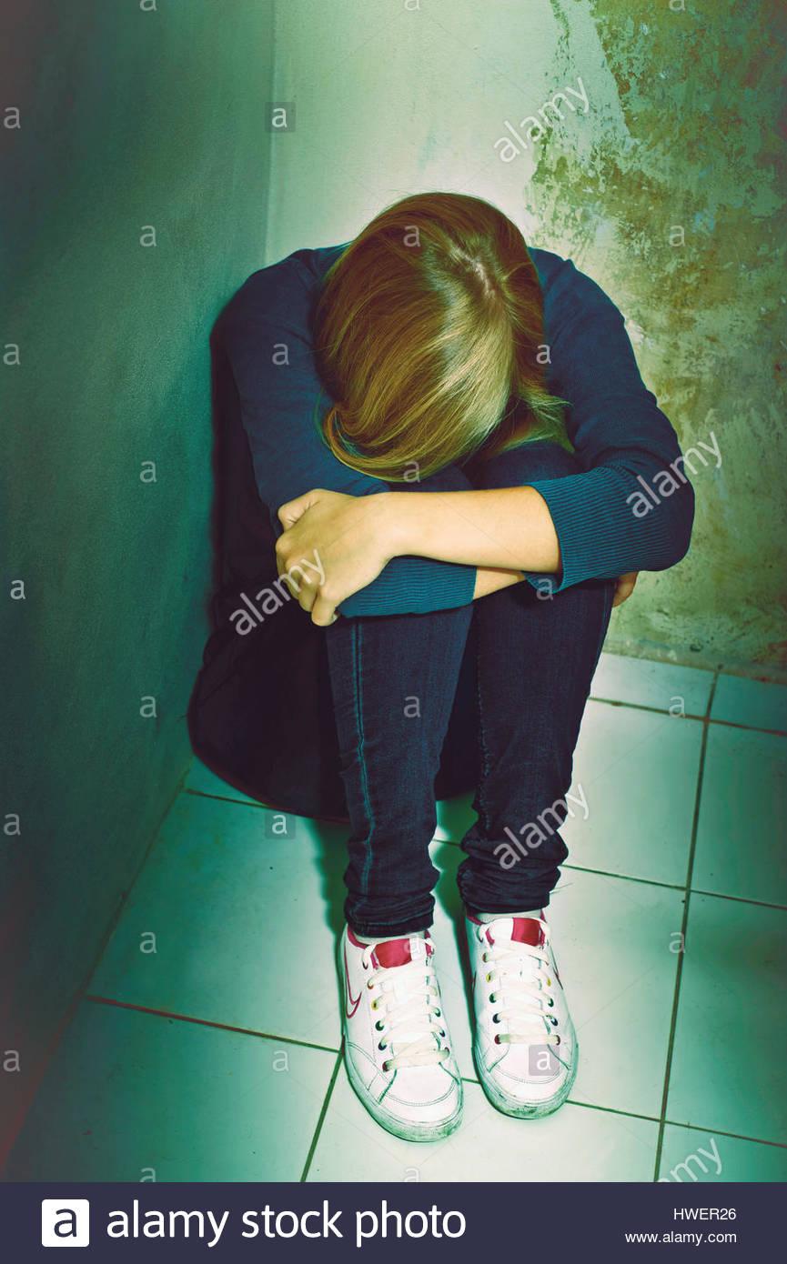 blonde Mädchen sitzt in einer Ecke verstecken ihr Gesicht Angst oder Angst, häusliche Gewalt oder Missbrauch Stockbild