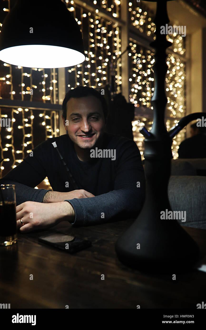 Mann hält Shisha Pfeife und Rauchen in einem Nachtclub Stockbild