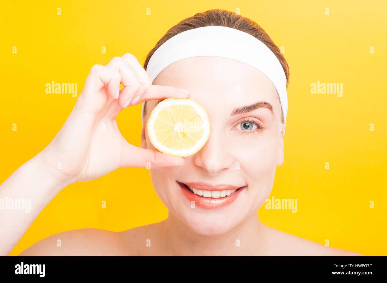 Natürliche Gesichtsmasken Konzept mit junge Frau und eine frische Zitronenscheibe auf gelbem Hintergrund Stockbild