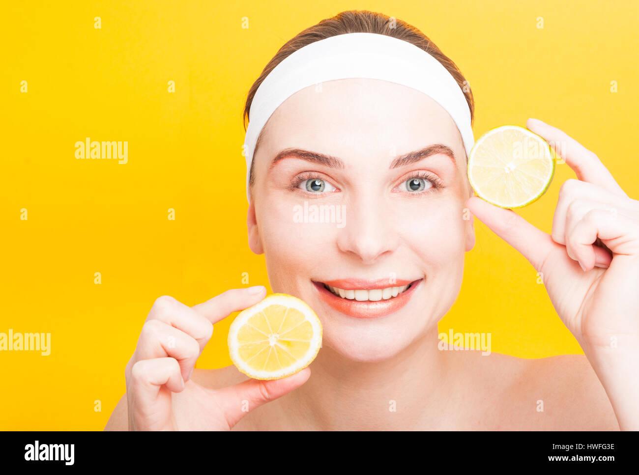 Haut Pflege und Schönheit Konzept mit fröhliche Frau, die Scheiben der Zitrone und Limone auf gelbem Hintergrund Stockbild
