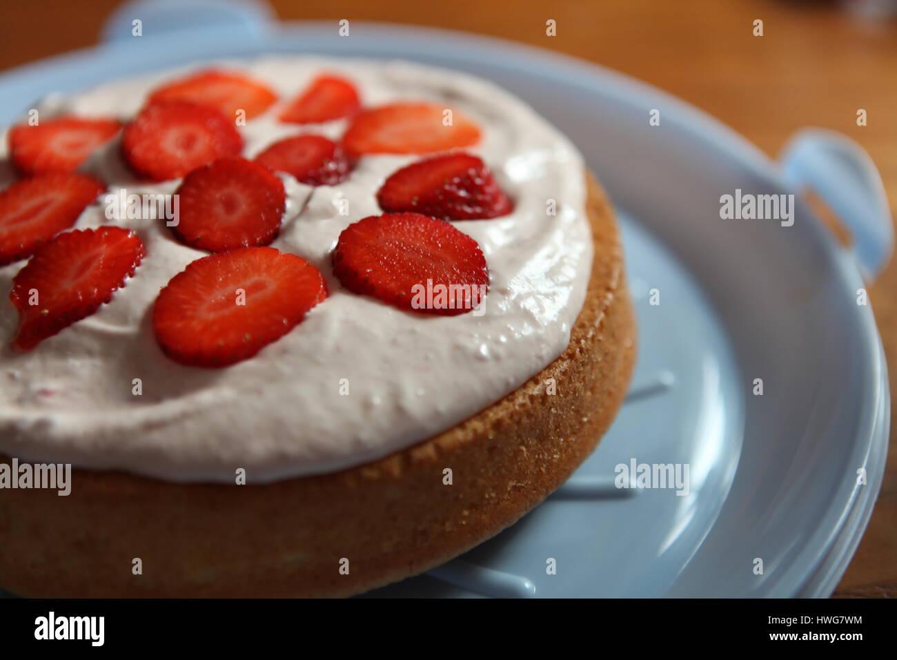 Die Mitte des Kuchens Erdbeeren hinzufügen Stockbild