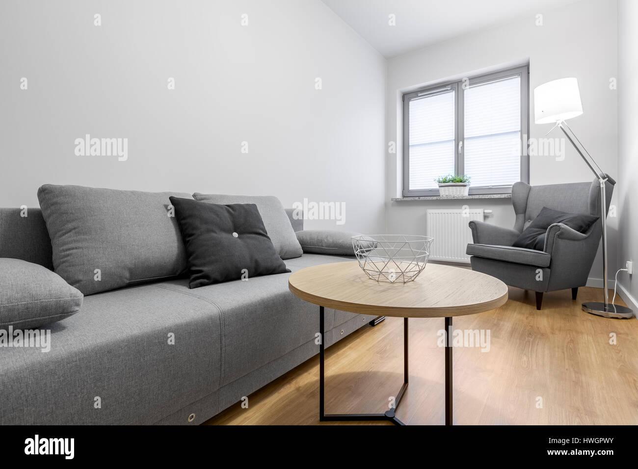 Kleines Wohnzimmer mit grauen Sofa, Sessel und Couchtisch ...