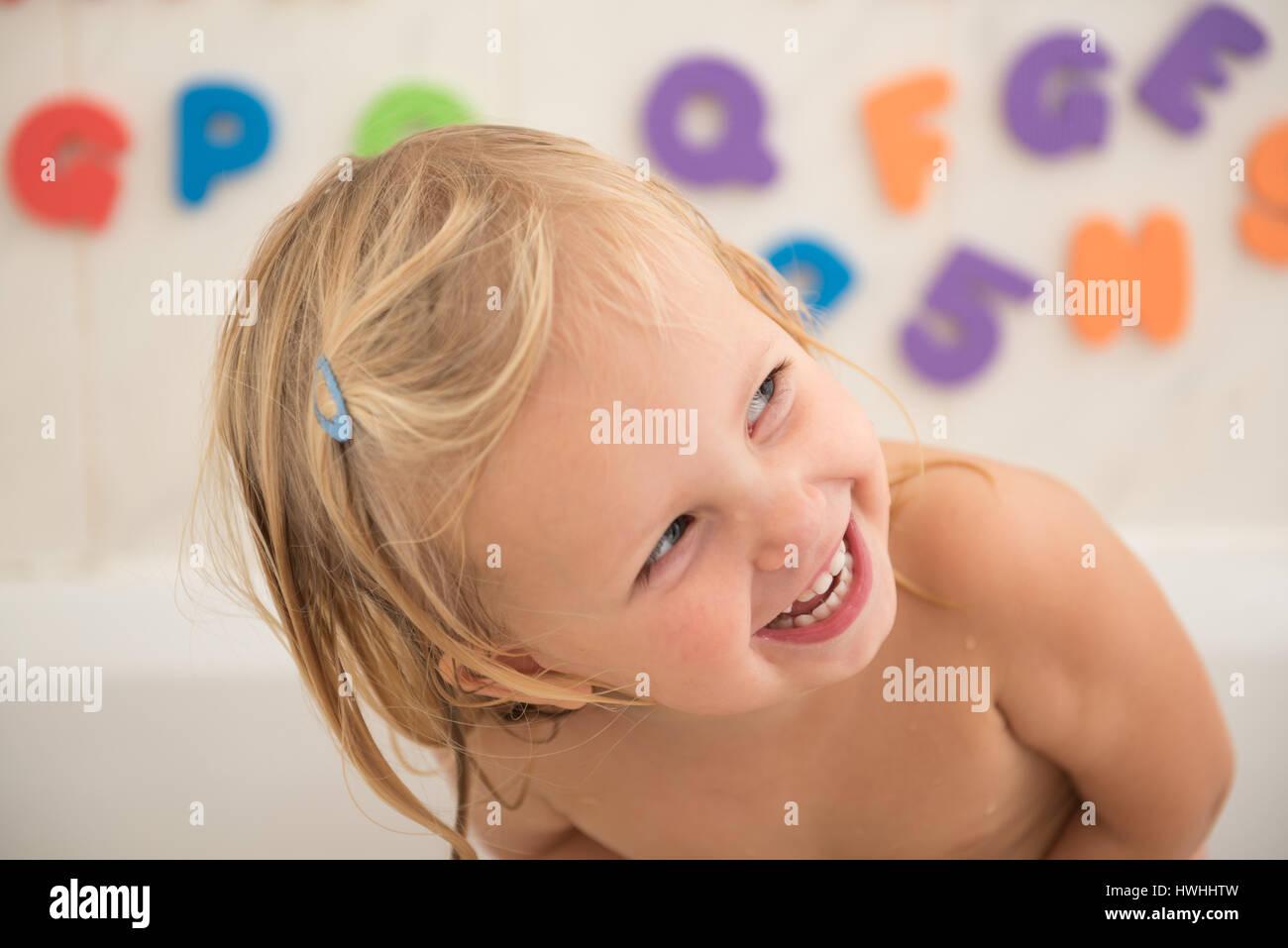Lächelndes Mädchen im Badezimmer mit bunten Schaum ...