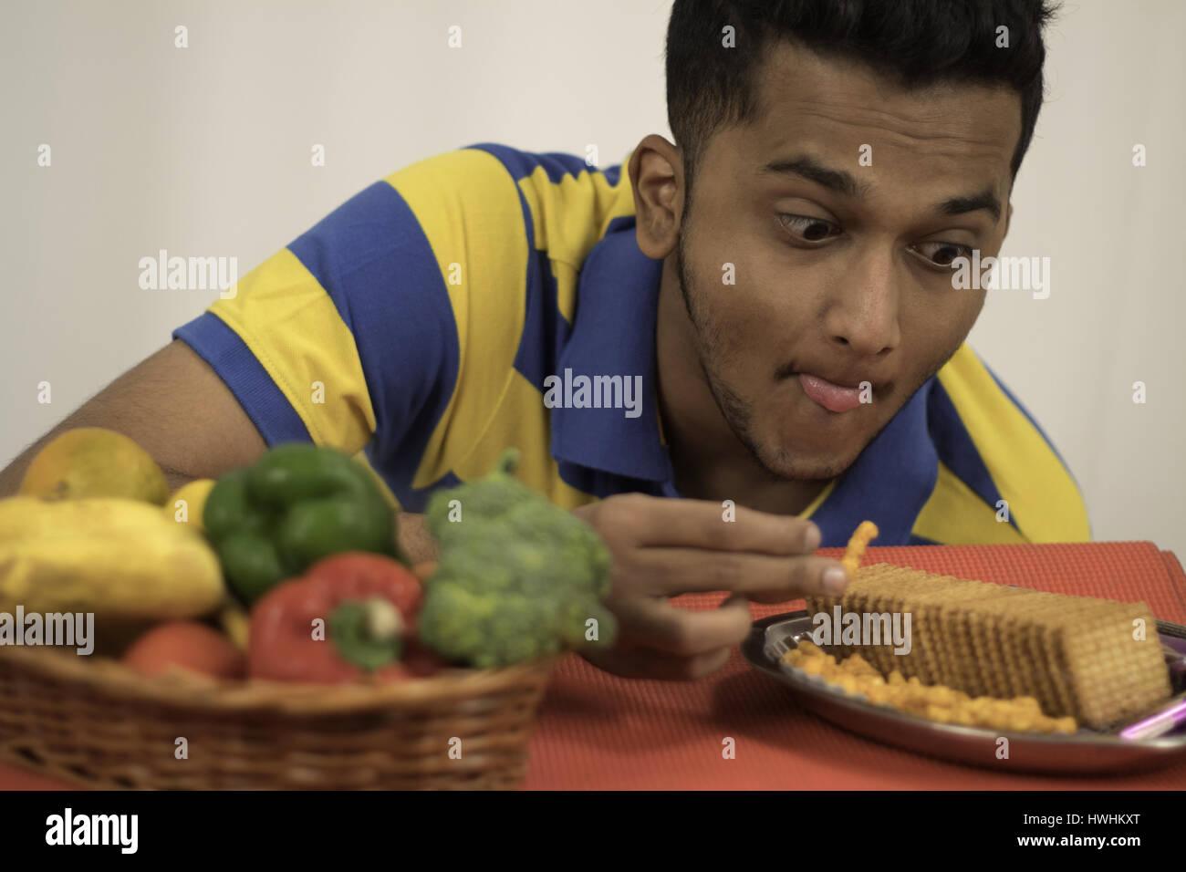 Mann, die Begierde der süß salzig ungesunde Lebensmittel über das gesunde Obst und Gemüse Korb Stockbild