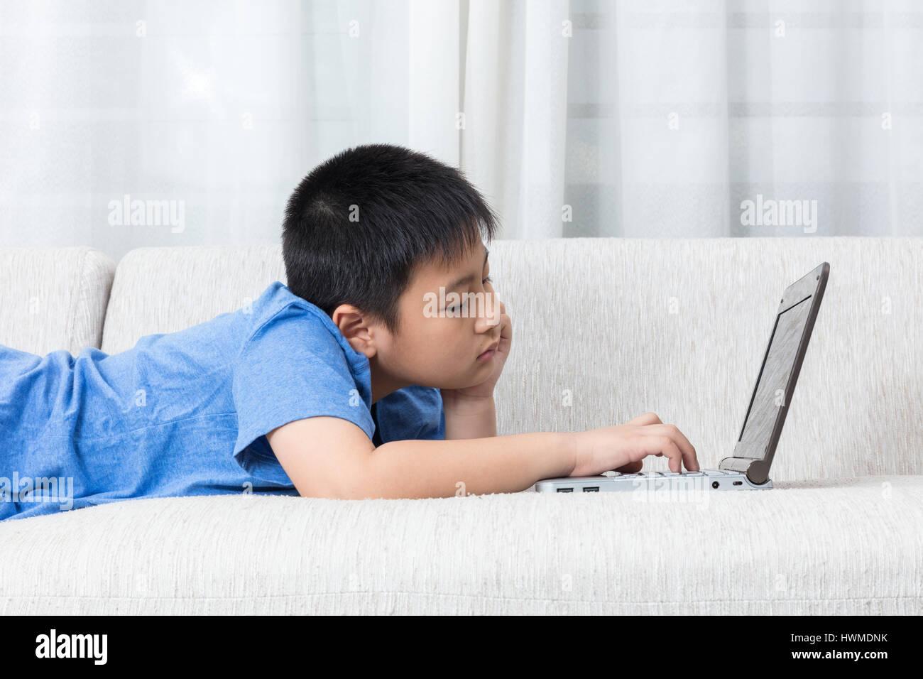 Gelangweilt asiatische chinesische kleiner Junge mit Laptop auf dem ...