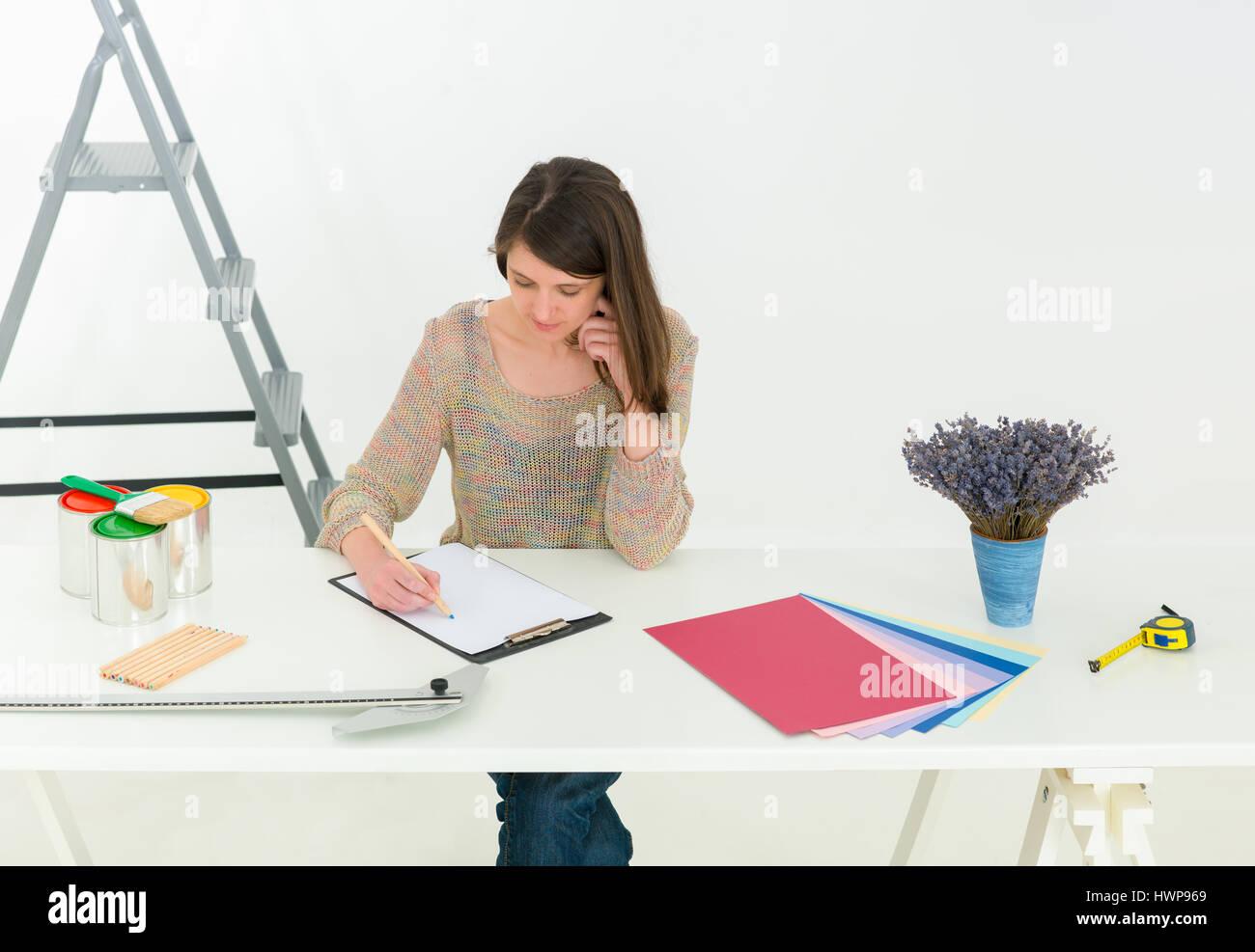 Kreative Menschen am Arbeitsplatz. Nahaufnahme der Brünette Junge Designer Frau mit Farbpalette am Schreibtisch Stockbild