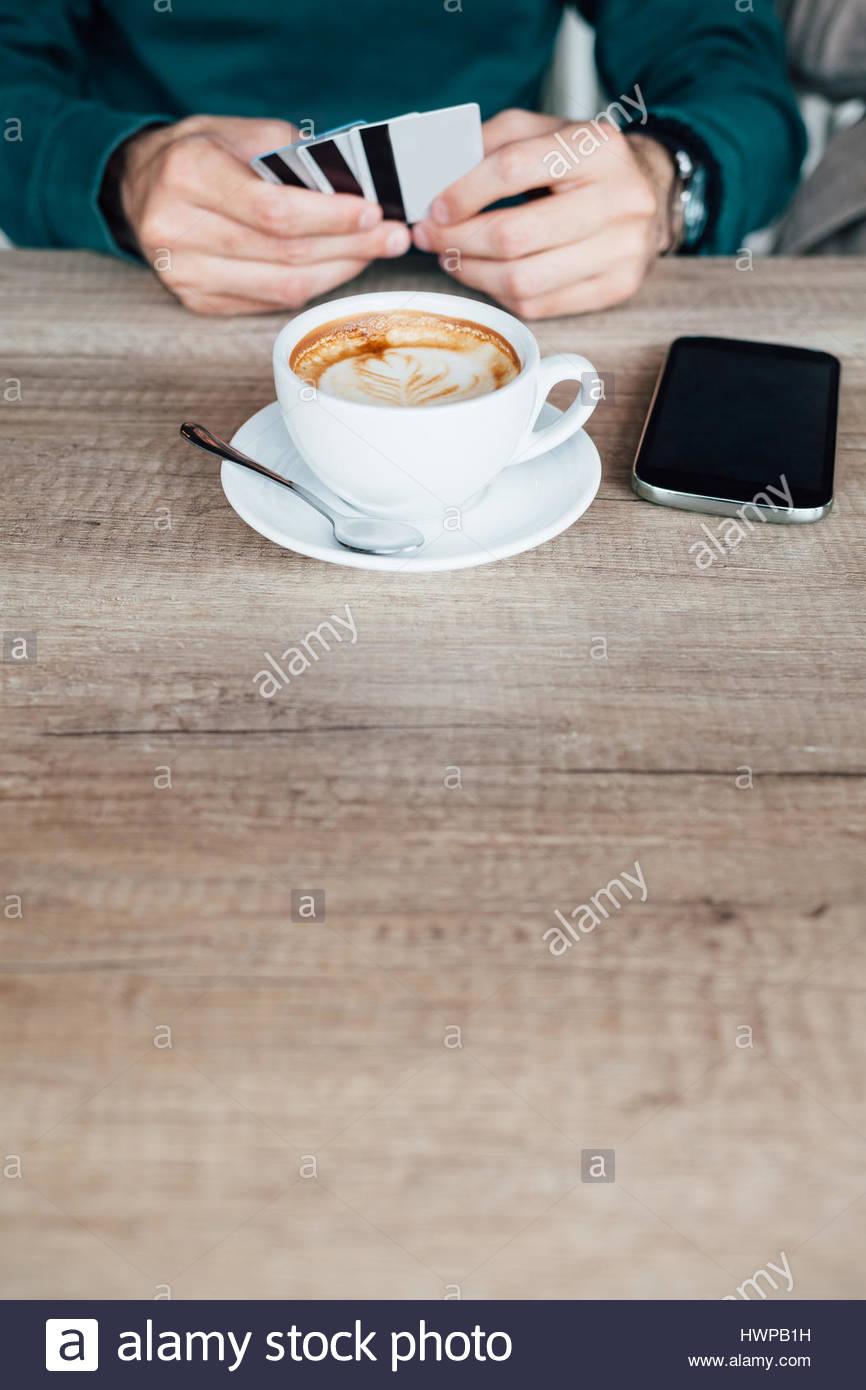 Man zahlt einen Kaffee mit Kredit-oder Bankkarte. Kopieren Sie auf Holztisch Platz. Stockfoto