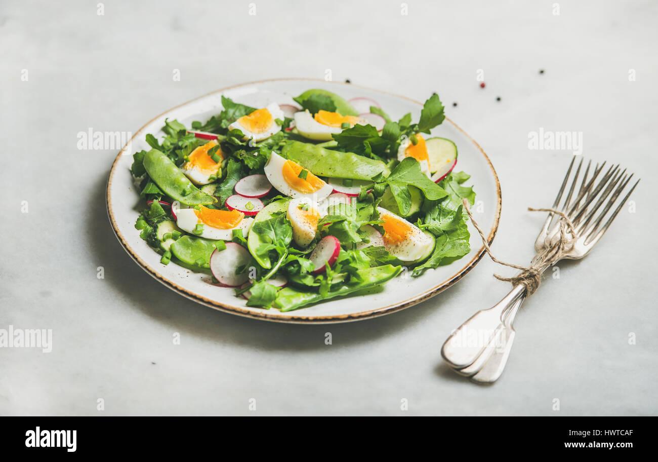 Gesundes Grün Frühlingssalat in weißer Teller auf grauem Hintergrund Stockbild