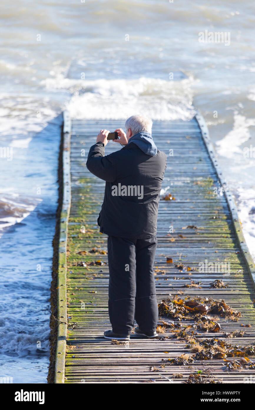 Ein Mann stand auf einem hölzernen Steg mit Wellen im beliebten ...