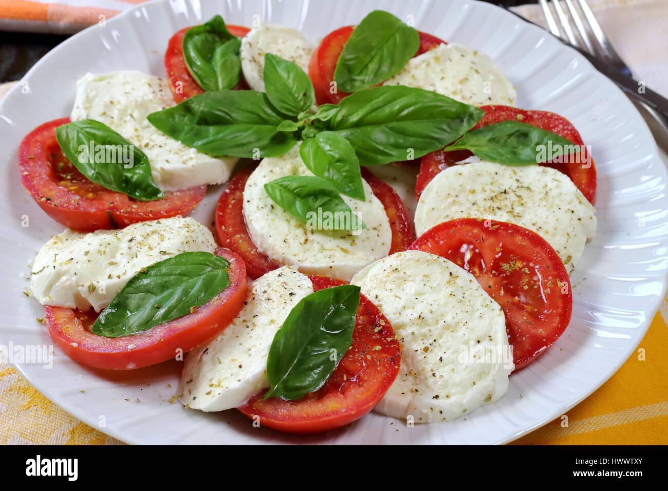 Tomaten und Büffel Mozzarella Caprese Sommer Salat hautnah mit Gabel im Hintergrund und frischem Basilikum Stockbild