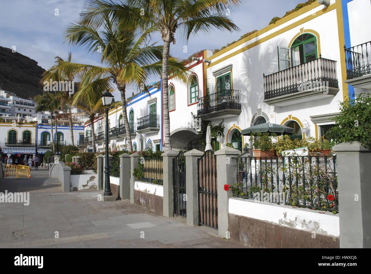 Weiße Häuser, Palmen, Blumen blühen in den Abendstunden. Blick auf die Straße, Puerto de Mogan, Gran Canaria, Spanien. Stockfoto
