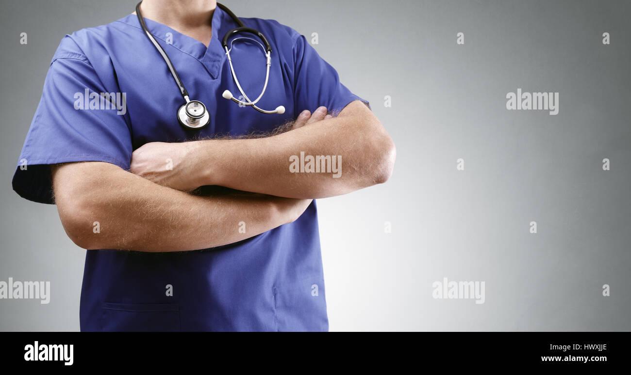Arzt in Scrubs Gelenkarme mit Stethoskop und grauen Hintergrund für Kopie Stockbild
