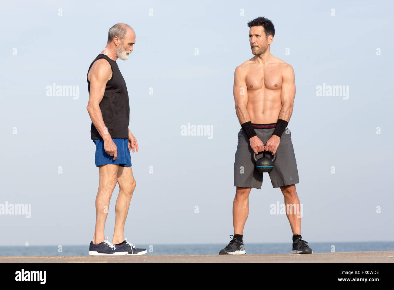 Athletischer Mann, die kettlebell Übung am Strand Stockbild