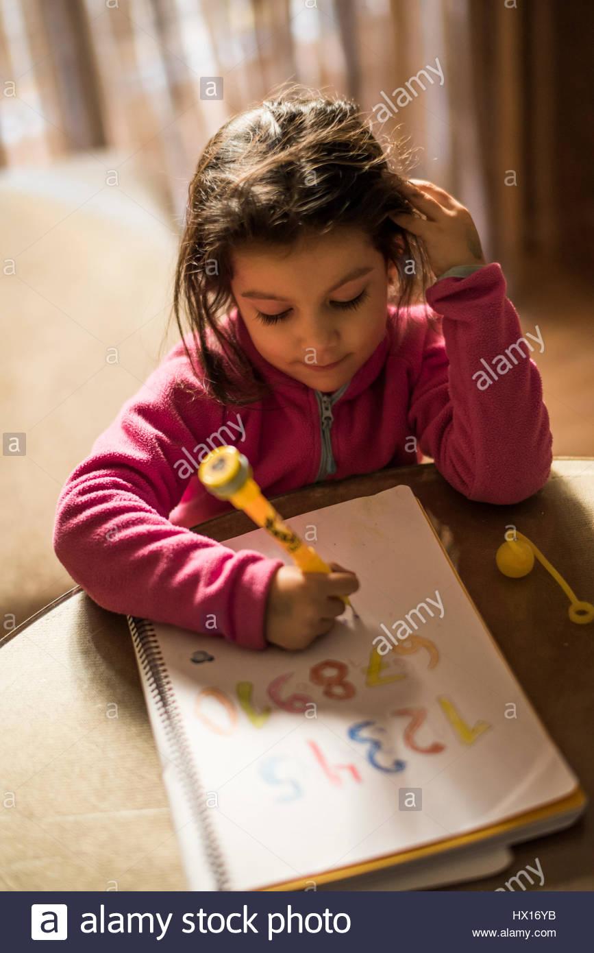 Kleine Mädchen zeichnen Zahlen Stockbild