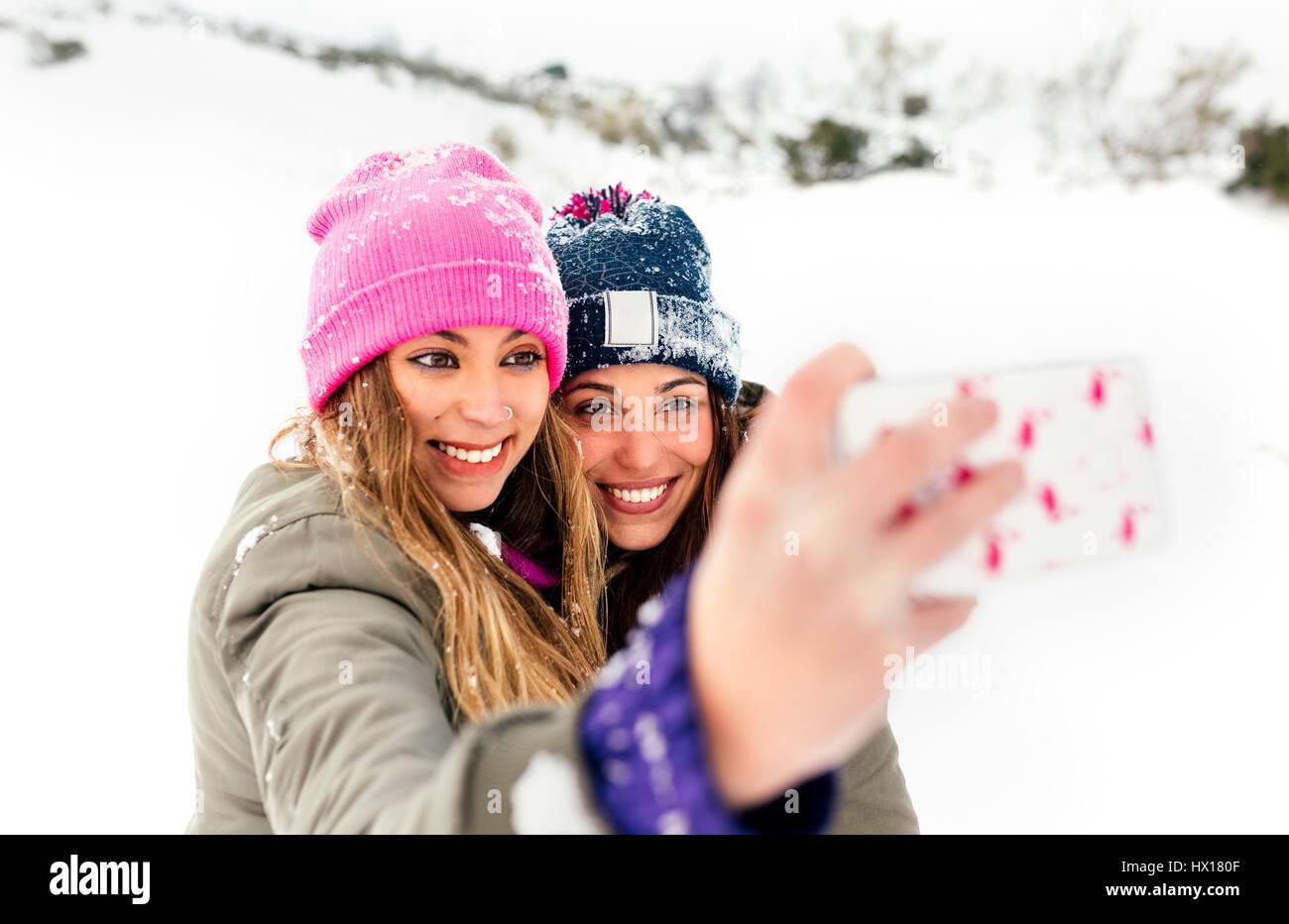 Zwei Freunde wobei Smartphone-Selfies im Schnee Stockbild
