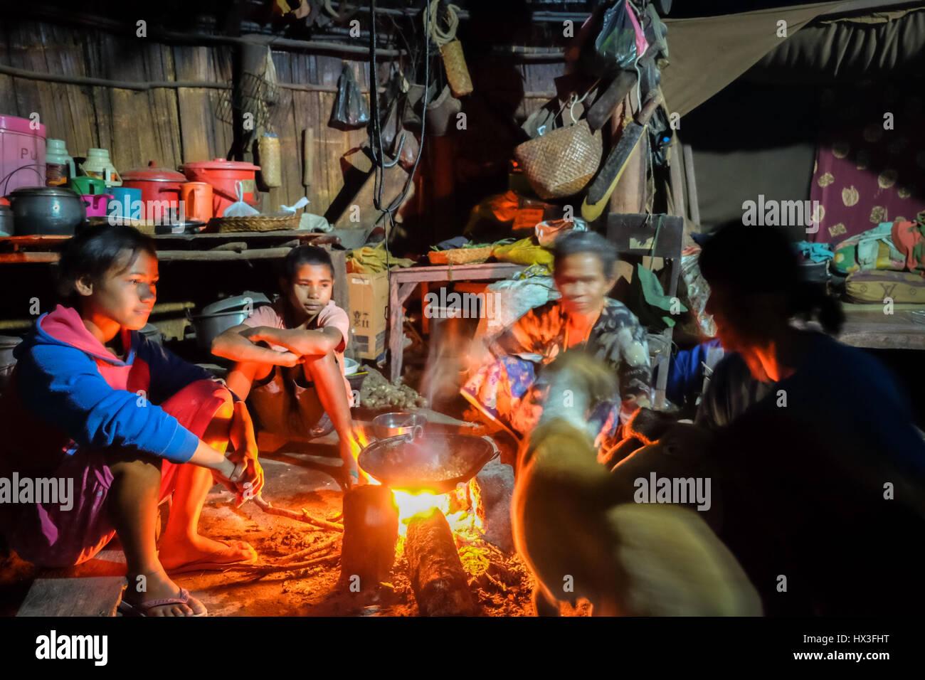 Ländliche Kinder haben ein Gespräch mit älteren Frauen in einem traditionellen Kücheraum in Stockbild