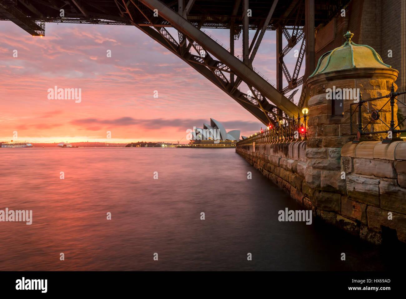 Sydney Opera House in der Morgendämmerung betrachtet unter der Sydney Harbour Bridge Stockbild