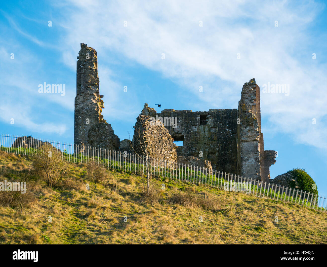 Wolkenfetzen und blauer Himmel über den historischen Remainds der Corfe Castle, Corfe Castle, Dorset, Großbritannien Stockbild