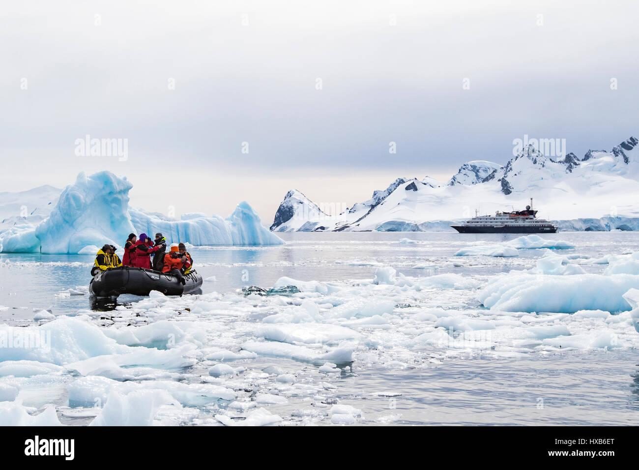 Antarktis Touristen im Tierkreis unter antarktischen Eisberges. Stockfoto