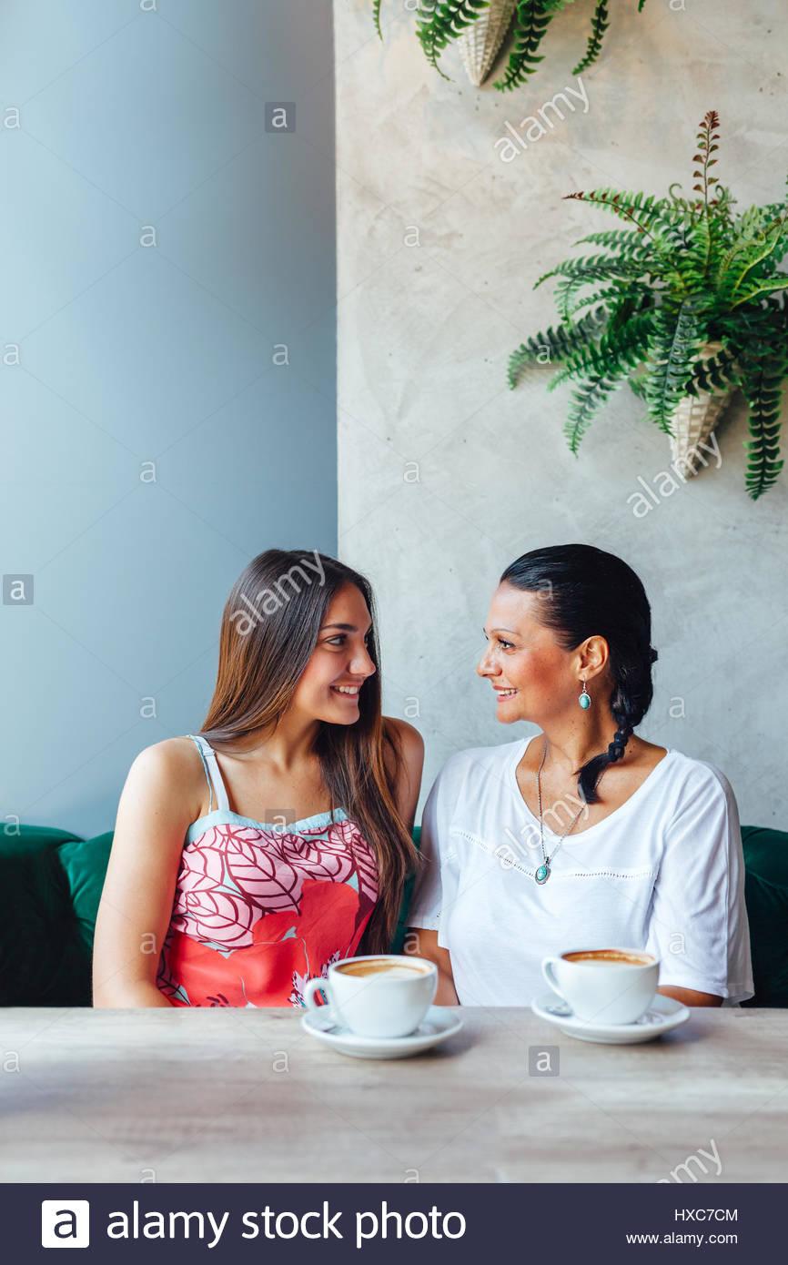 Zwei glückliche Frauen sprechen im Café. Im Alter von Frau und ihre erwachsene Tochter trinken Kaffee Stockbild