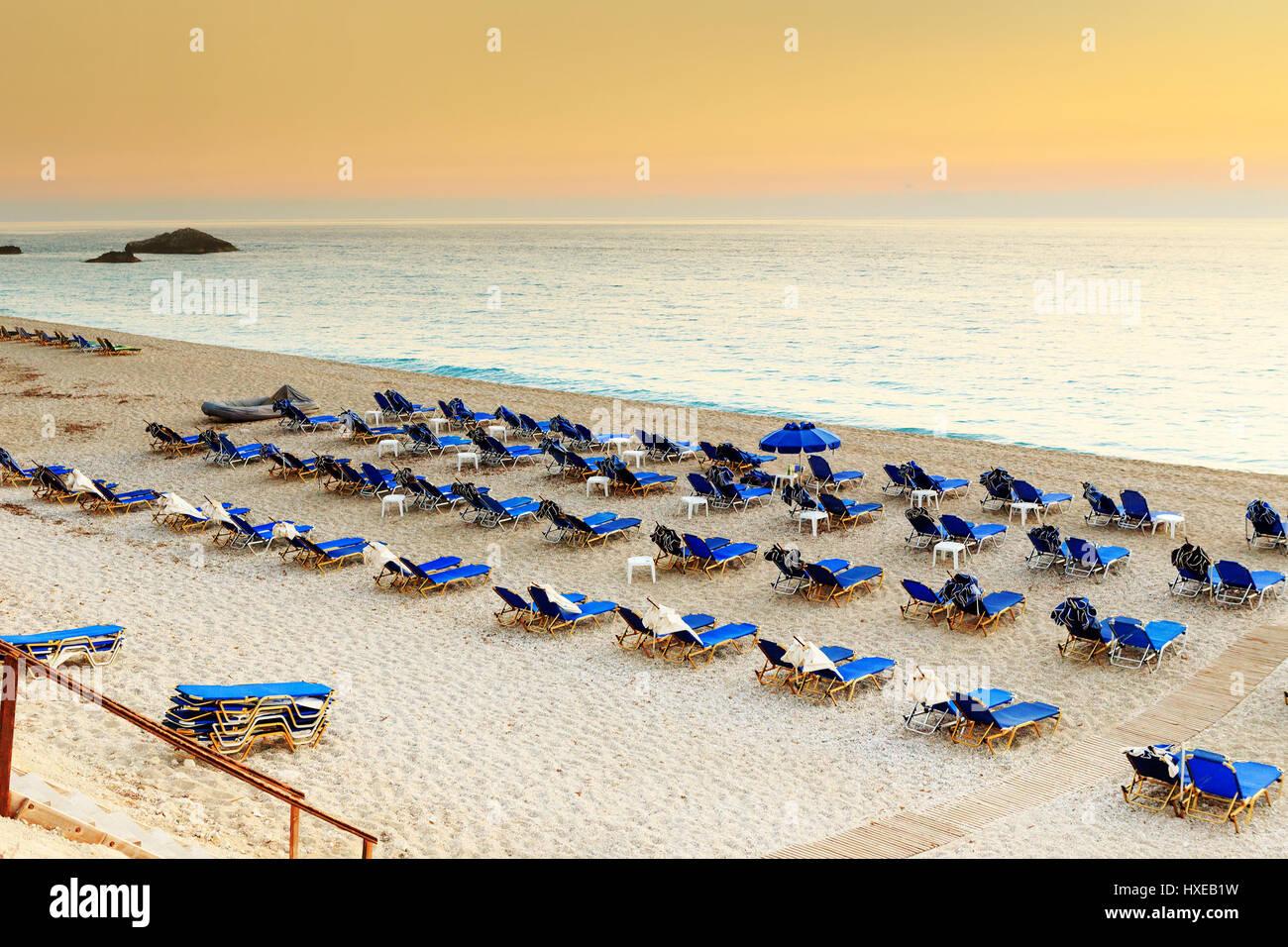 Liegen und Sonnenschirme am Strandresort in Griechenland, bei Sonnenuntergang Stockbild