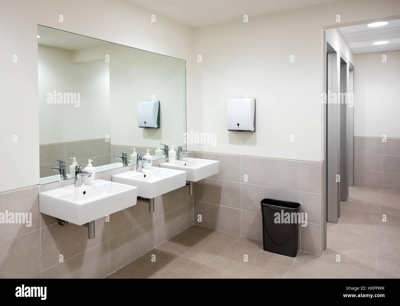 ffentliches bad oder toilette mit einer reihe von drei handwaschbecken mit seifenspender unter. Black Bedroom Furniture Sets. Home Design Ideas