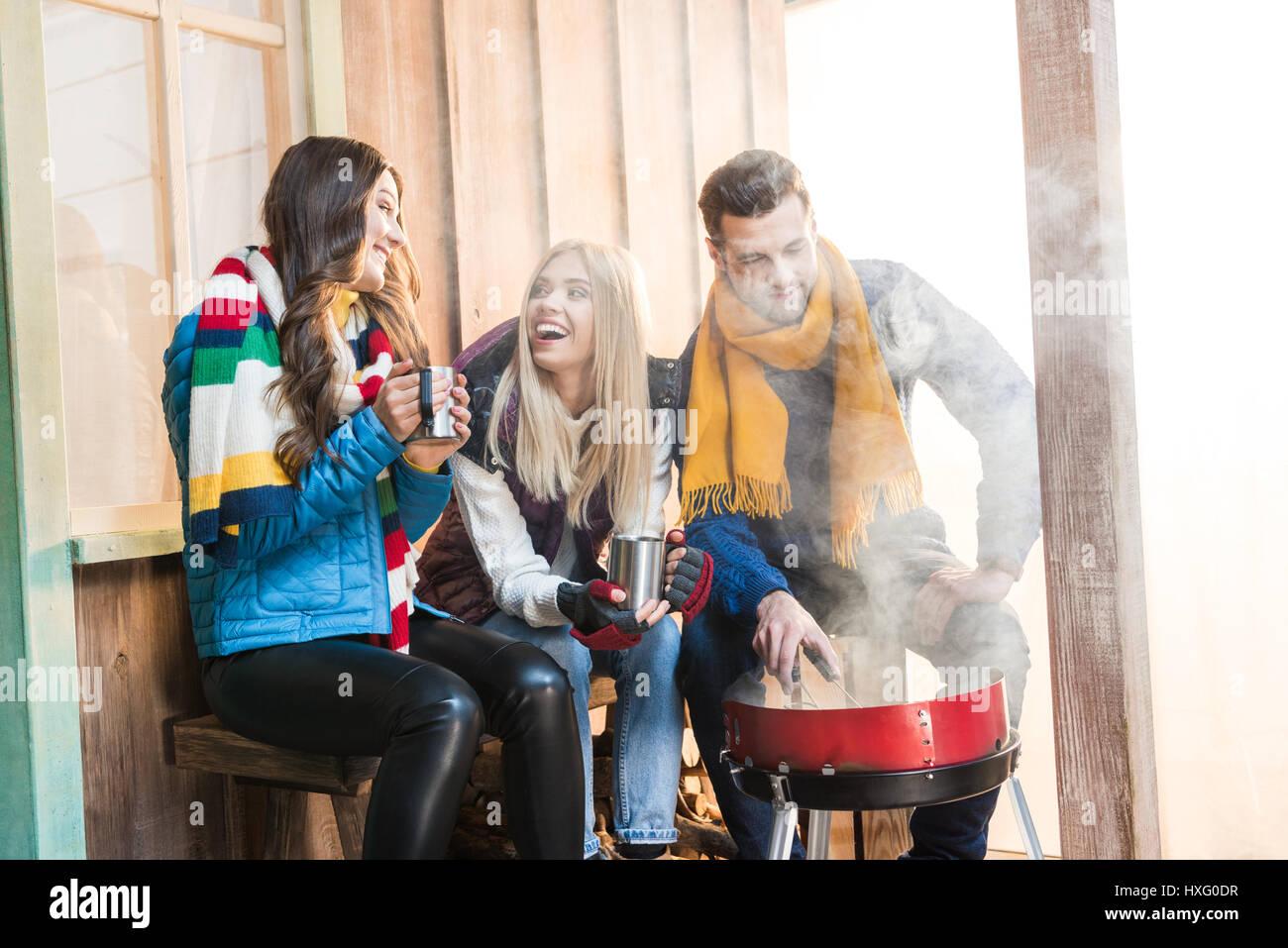 Glückliche junge Freunde heißen Tee trinken und Grillen von Fleisch auf Veranda Stockbild