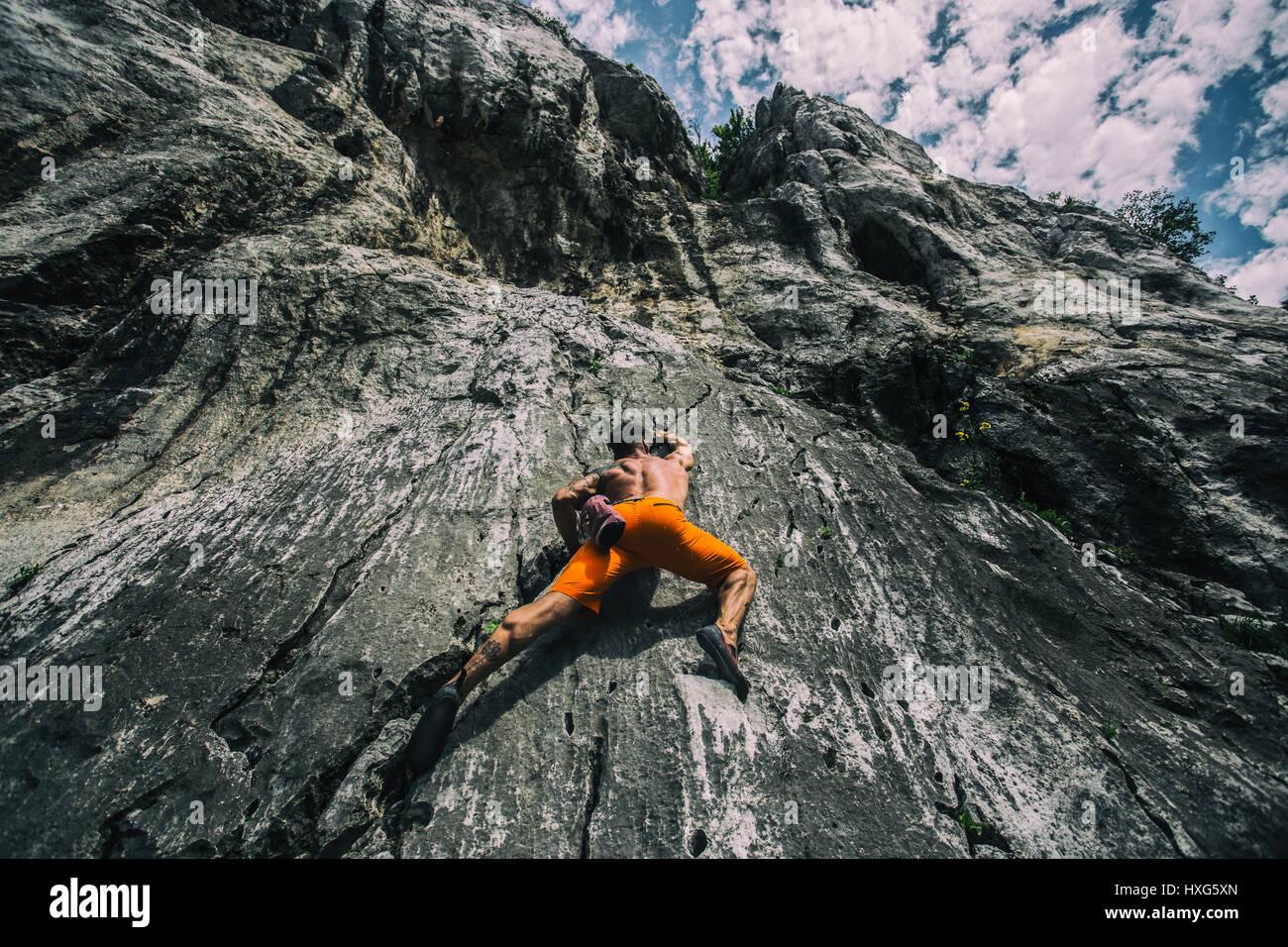 Athlet ist Felsen klettern. Stockbild