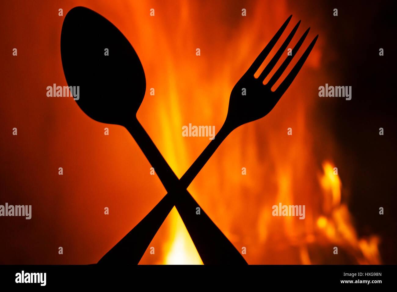 Gabel und Löffel auf einem Hintergrund von Feuer, Silhouetten, Hölle ...