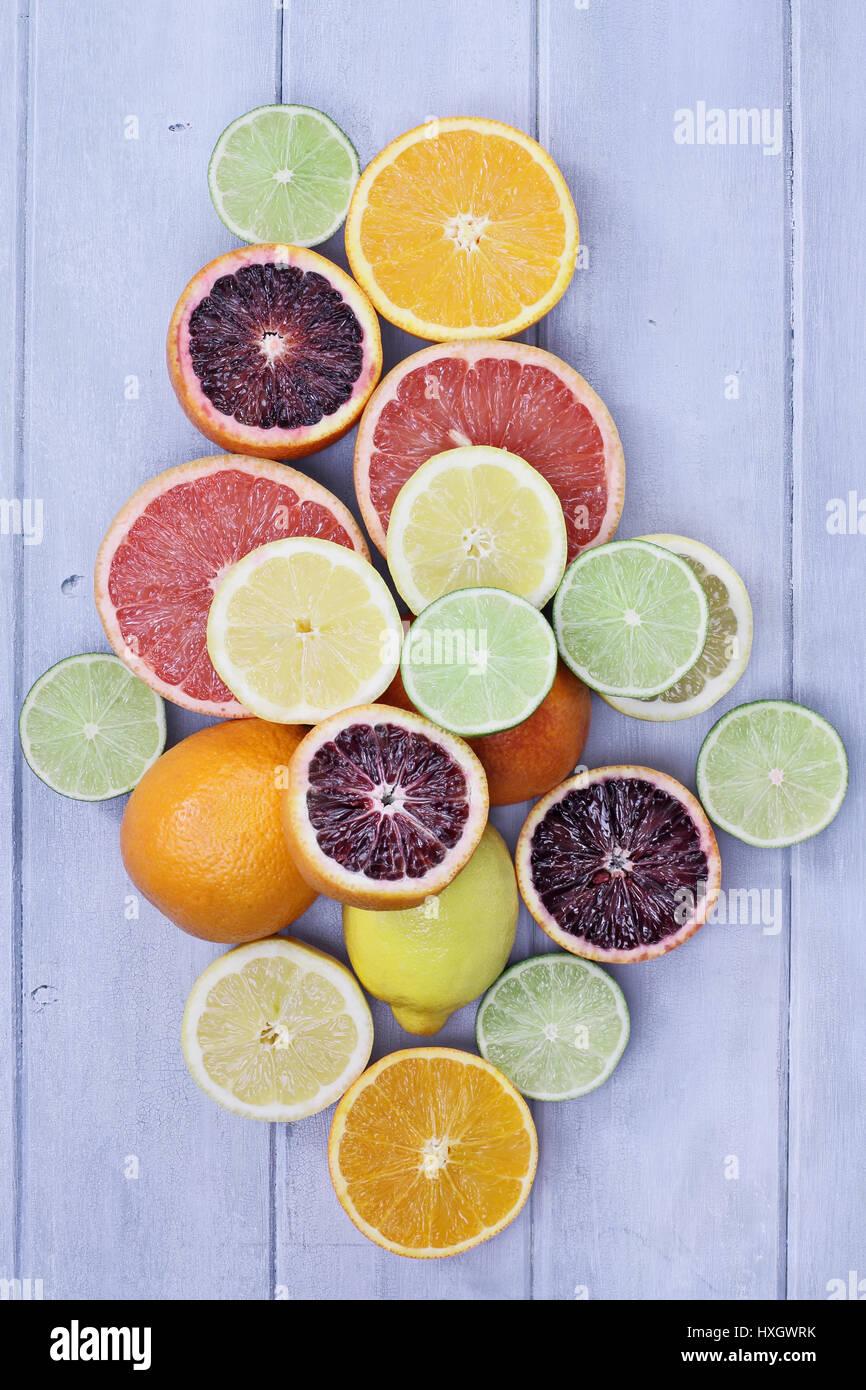 Vielzahl von Zitrusfrüchte (Orange, Blutorangen, Zitronen, Grapefruit und Limetten) über einen blauen Stockbild