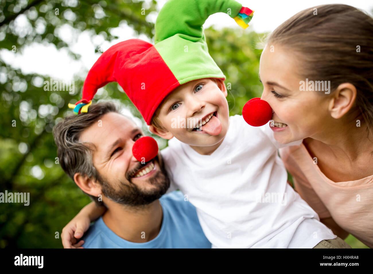 Kind Narr Kappe trägt und zeigt seine Zunge mit seiner Familie Stockbild
