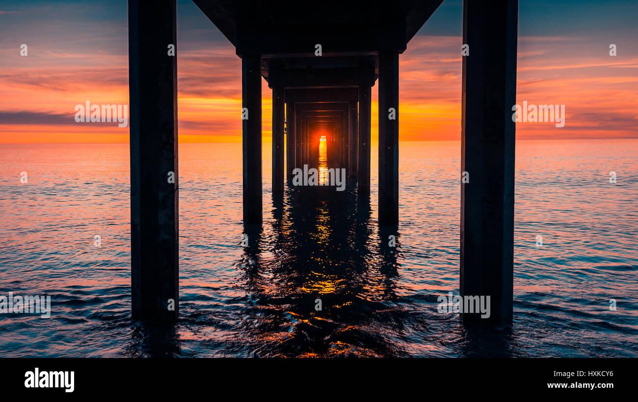 Sonnenuntergang betrachtet unter Brighton Pier, South Australia Stockbild