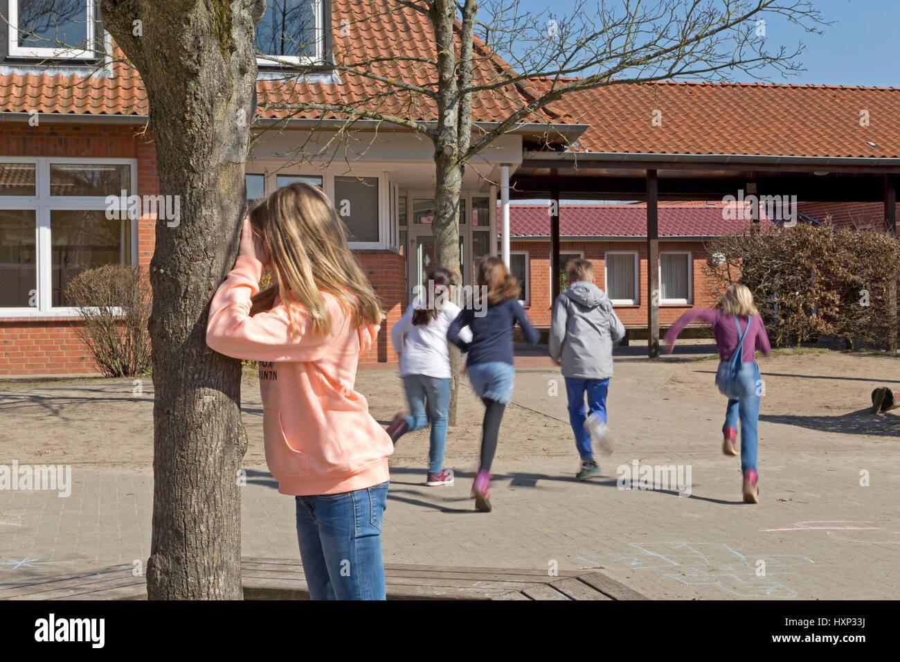 Kinder in der Grundschule spielen verstecken und suchen in Pause Stockfoto