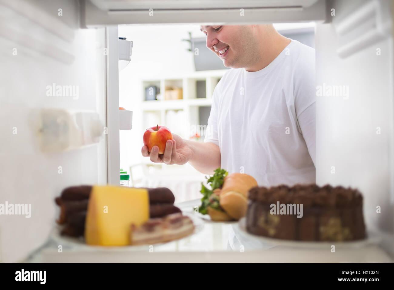 Dicker Mann auf Ernährung, richtige Wahl und Apfel aus Kühlschrank ...