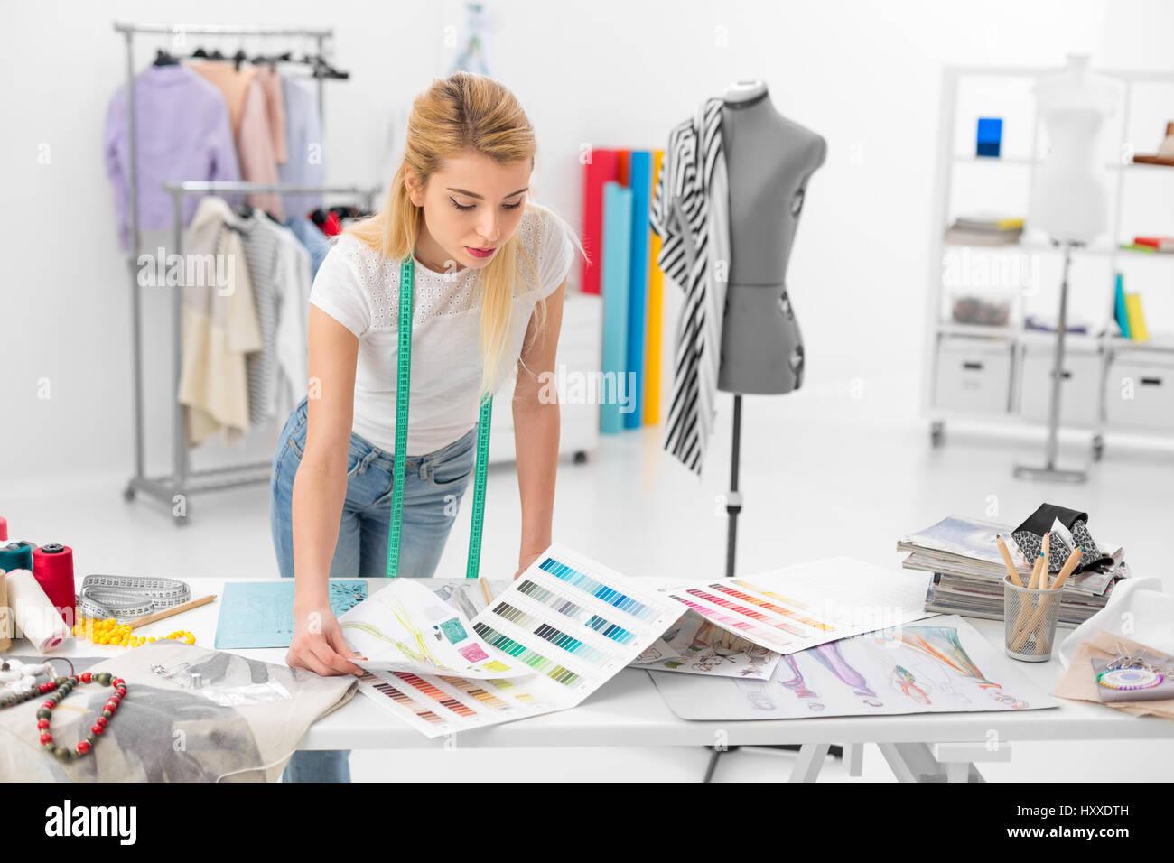 junge blonde Modedesignerin Frau Überprüfung Palette Farbmuster Stockbild