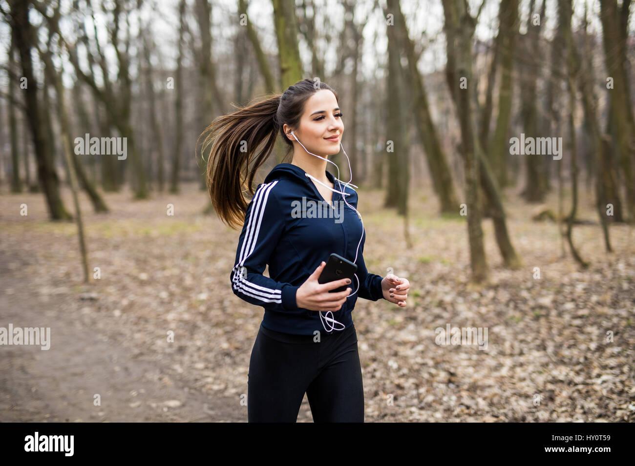 Junge Frau mit Kopfhörern im Park Joggen und auf Handy Stockbild