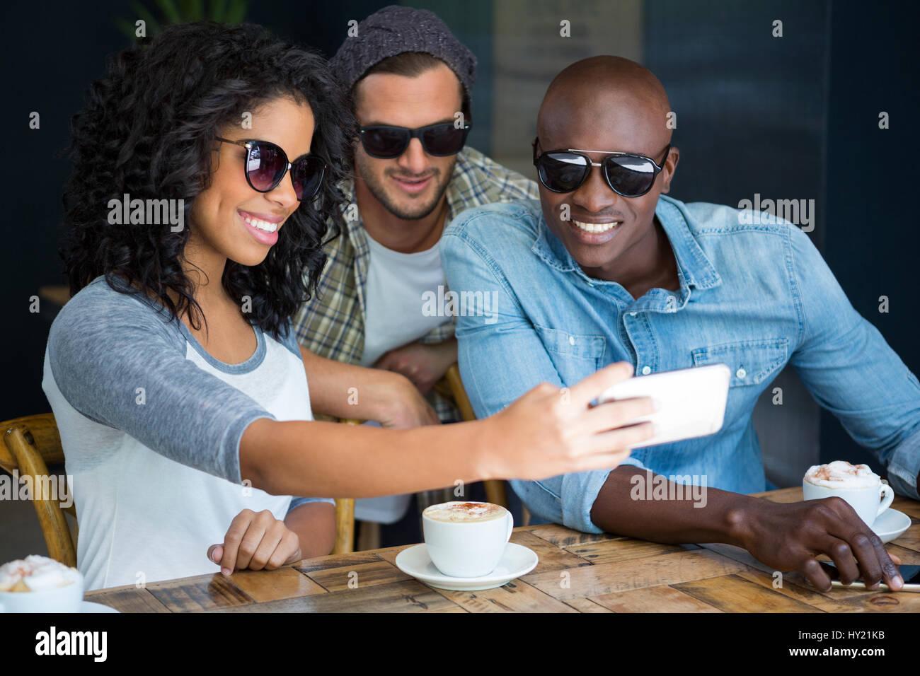 Glücklich Multi ethnischen Freunde Sonnenbrille während der Einnahme von Selfie in Coffee-shop Stockfoto