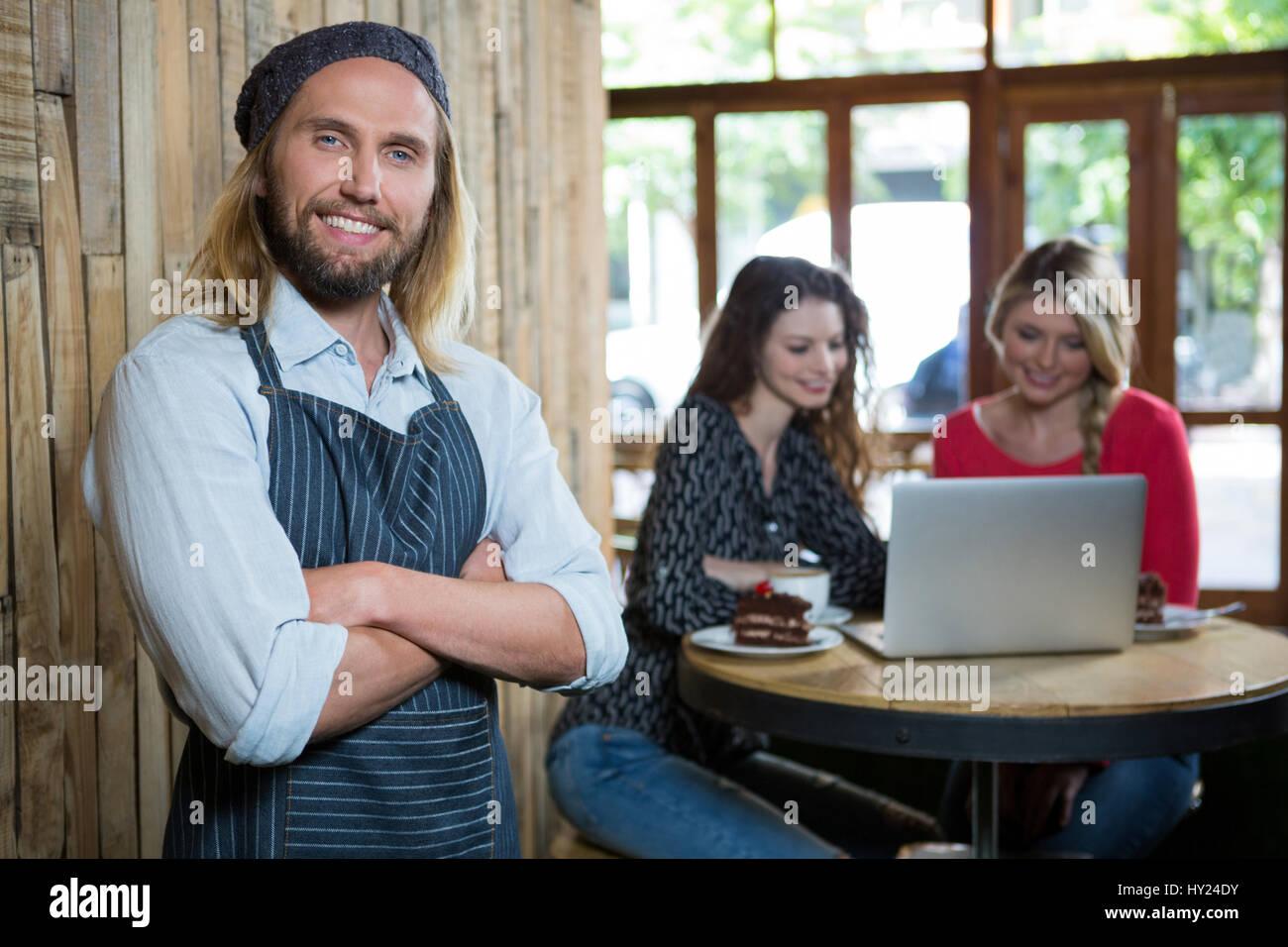 Porträt von zuversichtlich männliche Barista mit weiblichen Kunden im Hintergrund im café Stockfoto